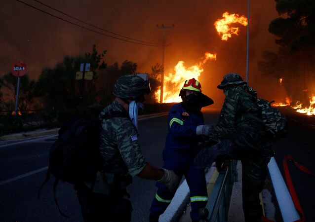 Firefighters and soldiers fall back as a wildfire burns in the town of Rafina, near Athens, Greece, July 23, 2018