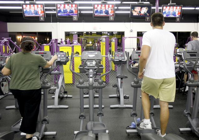 People exercise at Planet Fitness as President Obama delivers his speech on health care on Wednesday, Sept. 9, 2009 in Raleigh, N.C.