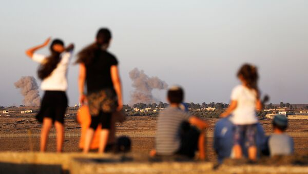 Israeli kids look over the Israeli Syrian border as smoke can be seen following an explosion at its Syrian side it is seen from the Israeli-occupied Golan Heights, Israel July 23, 2018 - Sputnik International