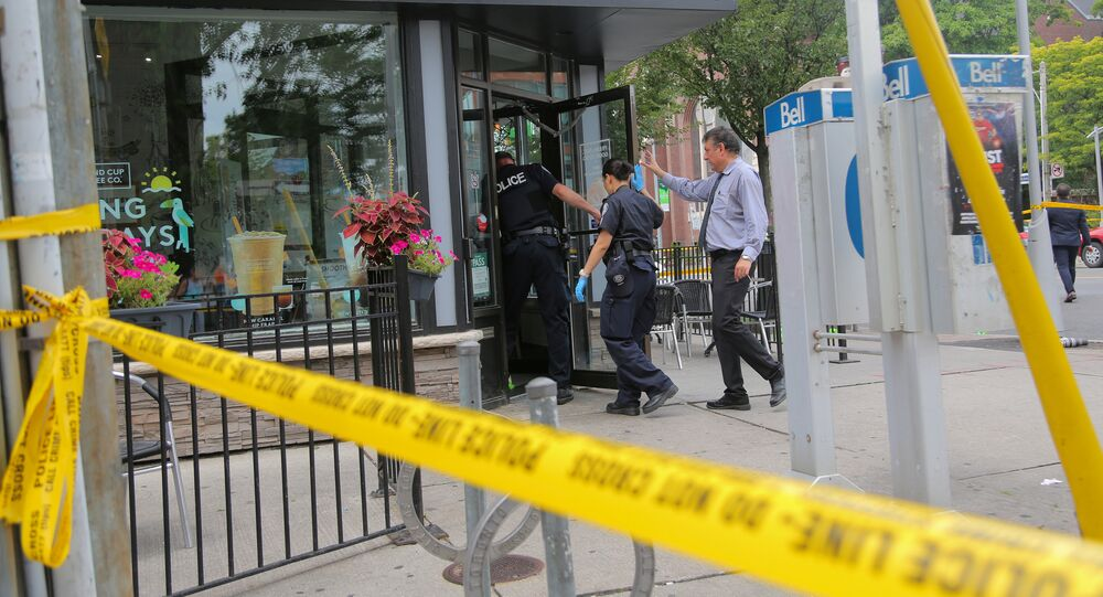 Police officers enter a coffee shop damaged by gunfire while investigating a mass shooting on Danforth Avenue in Toronto, Canada, July 23, 2018