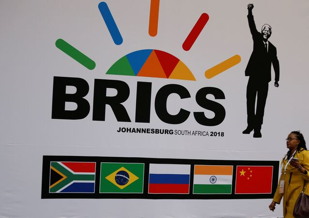 A delegate walks past a BRICS logo ahead of the 10th BRICS Summit, in Sandton, South Africa, July 24, 2018