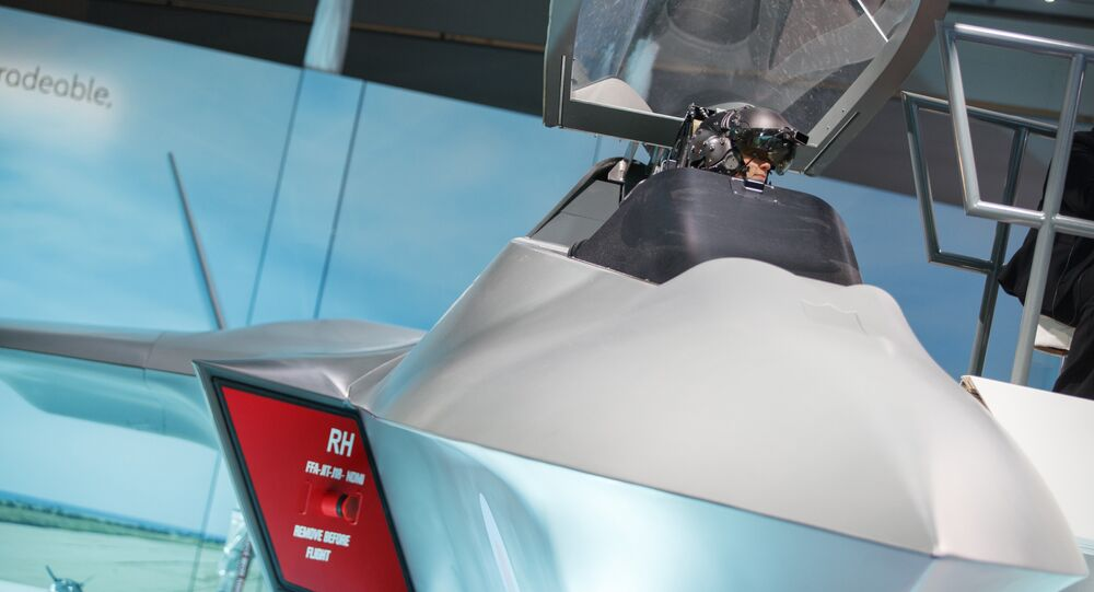 A visitor sits in the model of a new fighter jet, a part of Team Tempest, during the Farnborough Airshow, south west of London, on July 16, 2018