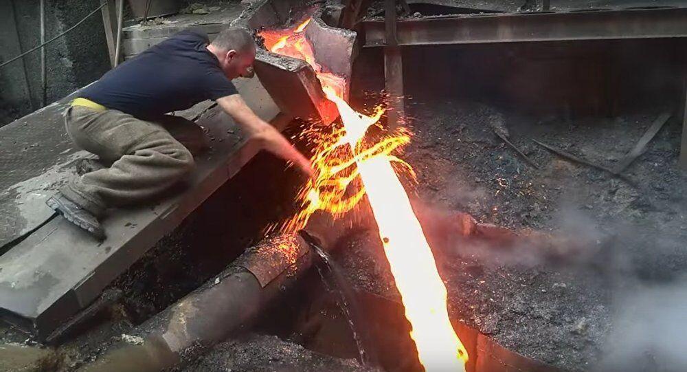 Steel Mill Worker Manhandles Molten Metal