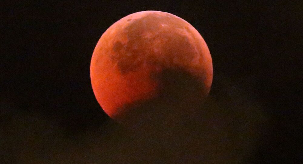 A blood moon rises during a complete lunar eclipse, in Hong Kong, Saturday, July 28, 2018. Curiosity and awe have greeted a complete lunar eclipse, the longest one of this century and visible in much of the world.