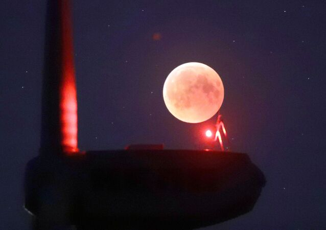 The blades from a wind turbine are silhouetted against the moon in the sky in Novogrudok, Belarus, during a total lunar eclipse on Saturday, July 28, 2018. Skywatchers around much of the world are looking forward to a complete lunar eclipse that will be the longest this century.