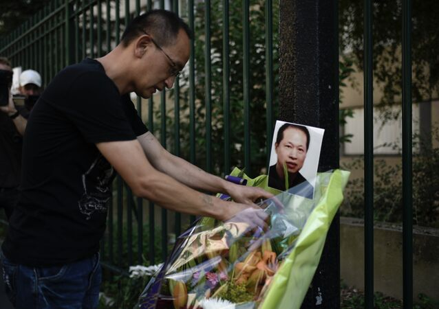 A member of the Chinese commmunity arranges a display of flowers besides a photograph of slain Chinese tailor Zhang Chaolin during a candlelight vigil in Aubervilliers on August 7, 2017, on the first anniversary of the fatal mugging of the Chinese tailor. Chinese tailor Zhang Chaolin, aged 49, was assaulted by three men in the streets in Aubervilliers on August 7, 2016 and died 5 days later from a coma.
