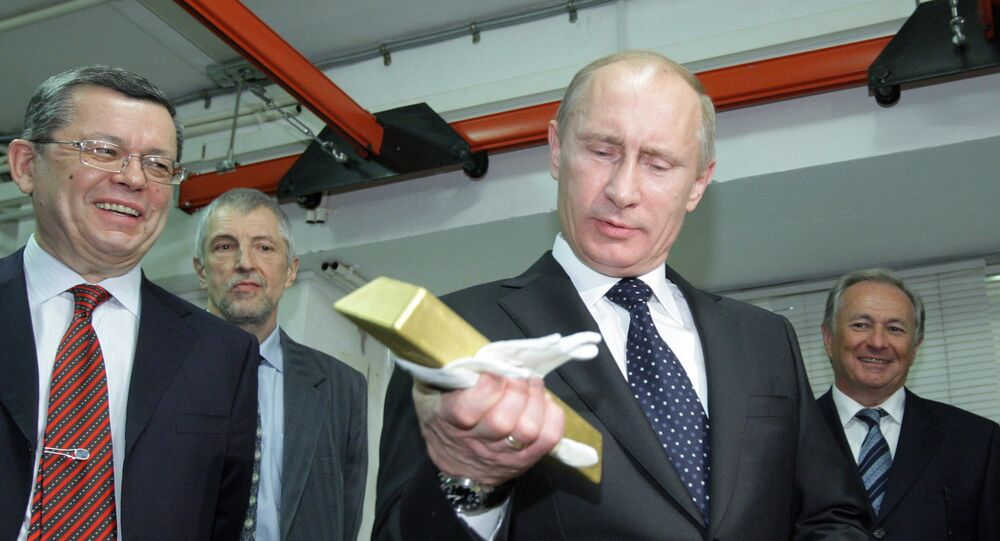 Vladimir Putin holding a gold bar while visiting the Central Depository of the Bank of Russia.
