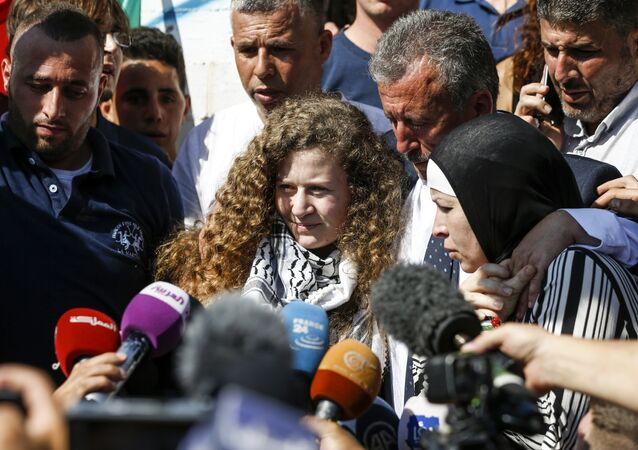 Palestinian activist and campaigner Ahed Tamimi (C) speaks to reporters upon her release from prison after an eight-month sentence for slapping two Israeli soldiers, on the outskirts of the West Bank village of Nabi Saleh on July 29, 2018, as she is accompanied by her father (C-R) and mother (R)