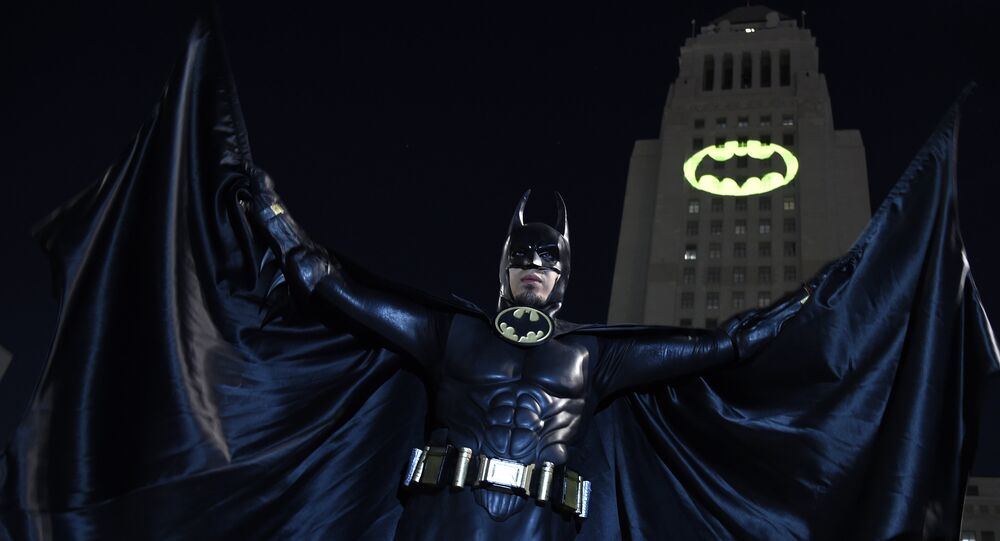 Caeser Saend, of Los Angeles, poses in front of a Bat-Signal projected onto City Hall at a tribute to Batman star Adam West on Thursday, June 15, 2017, in Los Angeles