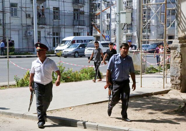 Police officers secure an area in the capital of Tajikistan, Dushanbe, where several Interior Ministry special forces officers and a traffic policeman were reportedly shot dead earlier on Friday, Sept. 4, 2015.