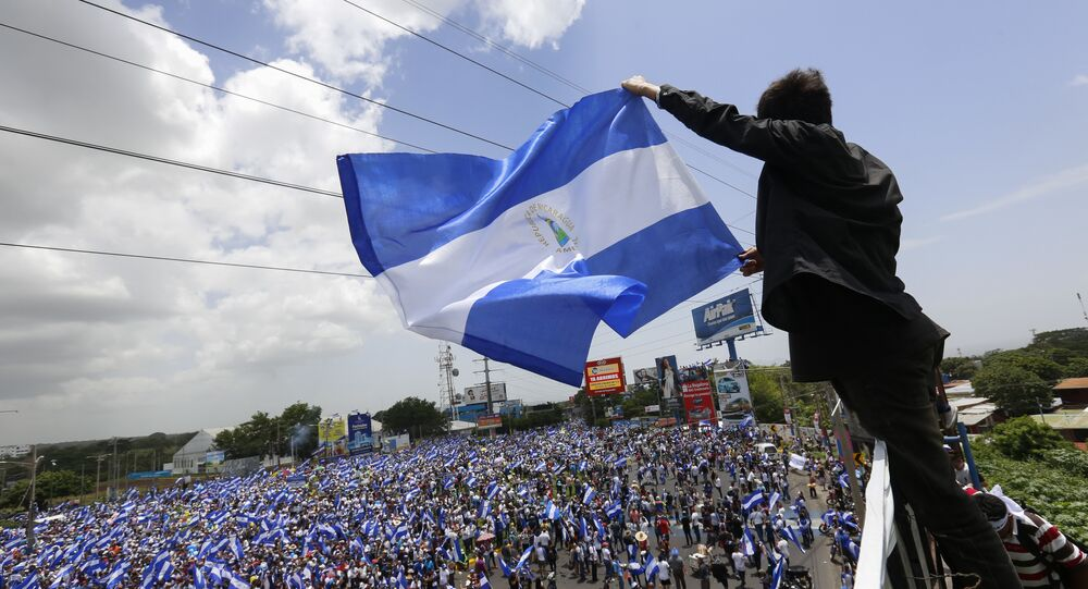A man waves a Nicaraguan flag as people participate in a demonstration