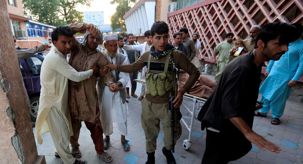 Men carry an injured man in a hospital after a suicide attack in Jalalabad, Afghanistan July 30, 2018