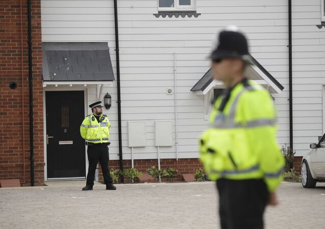 British police officers stand outside the front door of a residential property in Amesbury, England, Wednesday, July 4, 2018. British police have declared a major incident after two people were exposed to an unknown substance in the town, and are cordoning off places the people are known to have visited before falling ill