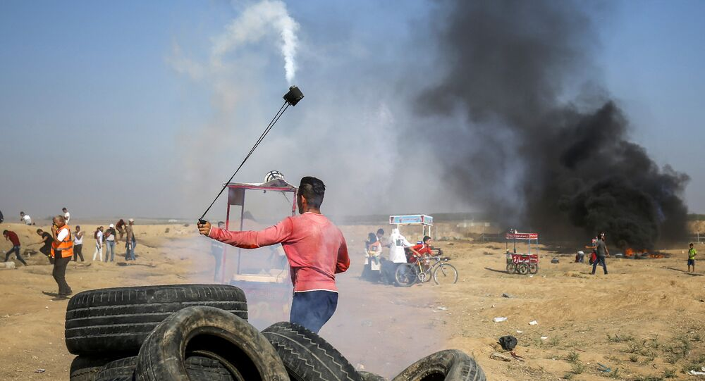 A Palestinian protester uses a slingshot to throw back a tear gas canister towards Israeli forces during clashes following a demonstration along the border east of Gaza City on July 6, 2018
