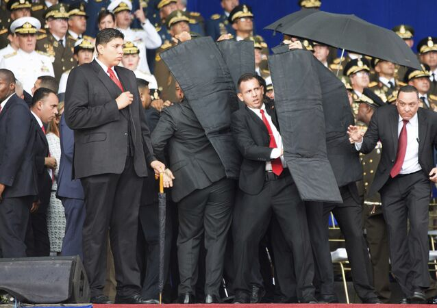 In this photo released by China's Xinhua News Agency, security personnel surround Venezuela's President Nicolas Maduro during an incident as he was giving a speech in Caracas, Venezuela, Saturday, Aug. 4, 2018