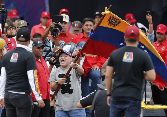 Argentina's former soccer star Diego Armando Maradona waves a Venezuelan flag during the closing campaign rally of President Nicolas Maduro in Caracas, Venezuela, Thursday, May 17, 2018. Maduro is seeking a new six-year mandate and despite crippling hyperinflation and widespread shortages of food and medicine, he is widely expected to win it in next May 20 election, that opponents have denounced as a fraud and have been condemned by much of the international community