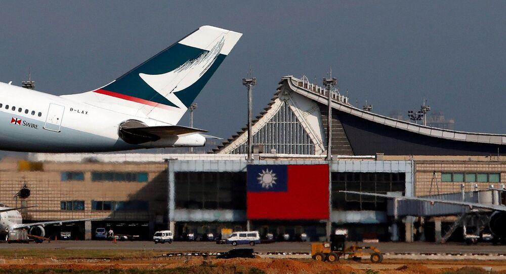 Hong Kong's Cathay Pacific Airways passenger plane takes off near a Taiwanese national flag at Taoyuan International Airport, Taiwan August 6, 2018