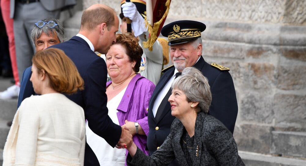 Britain's Prince William (2L) shakes hands with Britain's Prime Minister Theresa May in Amiens, northern France on August 8, 2018, as he arrives to attend a ceremony to mark the 100th anniversary of the World War I Battle of Amiens