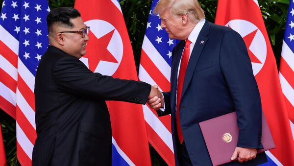 U.S. President Donald Trump and North Korea's leader Kim Jong Un shake hands during the signing of a document after their summit at the Capella Hotel on Sentosa island in Singapore June 12, 2018 - Sputnik International