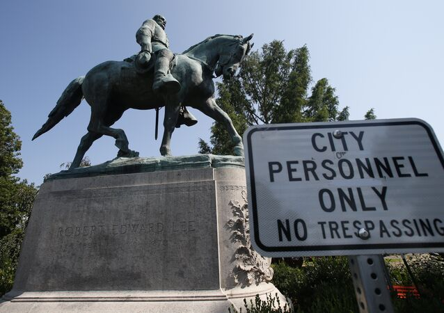 In this Monday, 6 August 2018 photo, a No Trespassing sign is displayed in front of a statue of Robert E. Lee in Charlottesville, Virginia, at the park that was the focus of the Unite the Right rally.