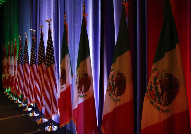 In this Aug. 16, 2017 file photo, the national flags of Canada, the U.S. and Mexico are lit by stage lights before a news conference, at the start of the North American Free Trade Agreement renegotiations in Washington