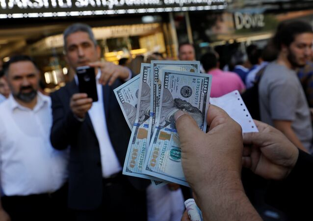 A businessman holding U.S. dollars poses for his friend in front of a currency exchange office in response to the call of Turkish President Tayyip Erdogan on Turks to sell their dollar and euro savings to support the lira, in Ankara, Turkey August 14, 2018