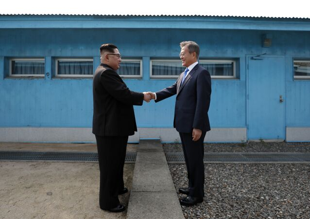 (FILES) This file photo taken on April 27, 2018 shows North Korea's leader Kim Jong Un (L) shaking hands with South Korea's President Moon Jae-in (R) at the Military Demarcation Line that divides their countries ahead of their summit at the truce village of Panmunjom