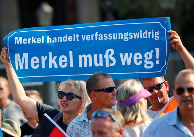 People hold a banner reading: Merkel is acting unconstitutionally, Merkel must leave as they take part in a protest against German Chancellor Angela Merkel as she visits the state parliament in Dresden, Germany August 16, 2018.