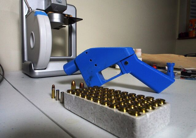 a Liberator pistol appears next to the 3D printer on which its components were made.