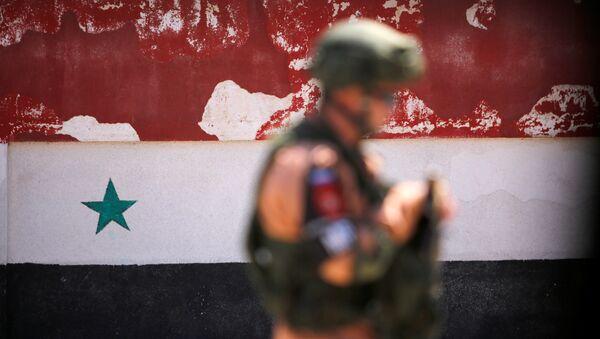 A Russian soldier stands guard near a Syrian national flag - Sputnik International