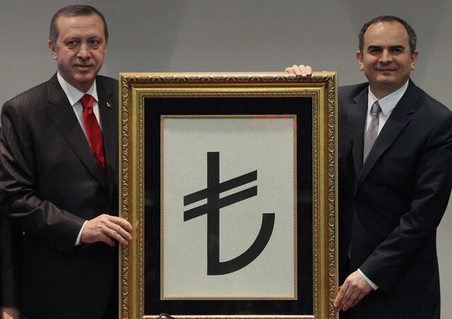 Turkish Prime Minister Recep Tayyip Erdogan, left, and former Central Bank Governor Erdem Basci show the symbol for the national currency, the Turkish lira, in Ankara, Turkey.