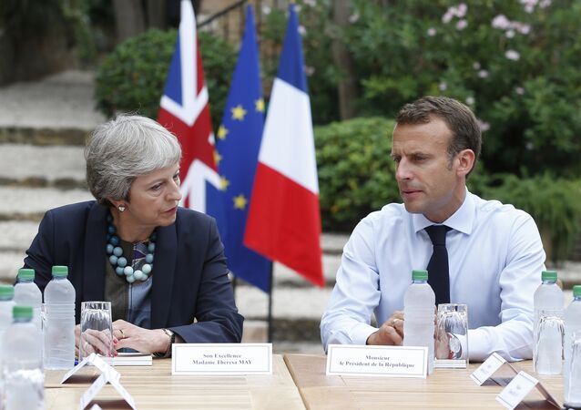 French President Emmanuel Macron, right, meets with British Prime Minister Theresa May to discuss Brexit issues at the Fort de Bregancon in Bornes-les-Mimosas, southern France, Aug. 3, 2018