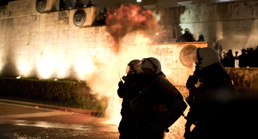 A petrol bomb thrown by protesters explodes behind riot police during a rally outside the Greek Parliament in Athens, Monday, Jan. 15, 2018. Greek lawmakers, eying the end of eight years of bailout programs, approved more painful austerity measures late Monday, as strikes and mass protests brought much of Athens to a standstill