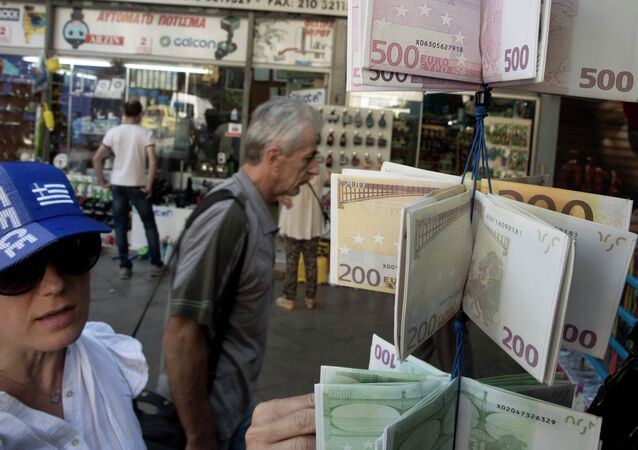 Una mujer en una gorra de colores de bandera griega mira a carteras diseñadas como las billetes de euro en Atenas
