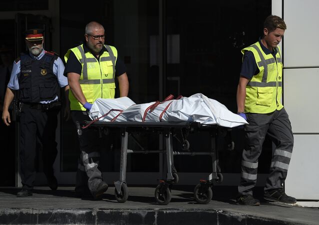 The body of a man who tried to attack a police station is carried out of the premises in Cornella near the northeastern Spanish city of Barcelona on August 20, 2018