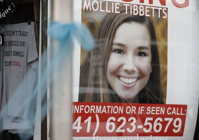 A poster for missing University of Iowa student Mollie Tibbetts hangs in the window of a local business, Tuesday, Aug. 21, 2018, in Brooklyn, Iowa