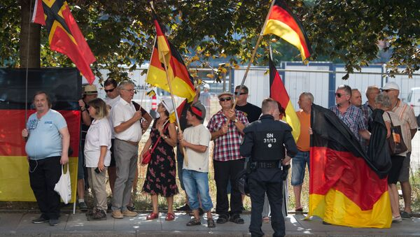 This picture taken on August 16, 2018 in Dresden, eastern Germany, shows anti-Islam Pegida movement supporters demonstrating on the occasion of German Chancellor's visit at the Saxon state parliament - Sputnik International