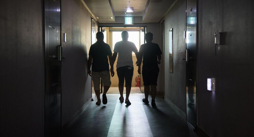 A group of asylum seekers walk along a hallway (File)