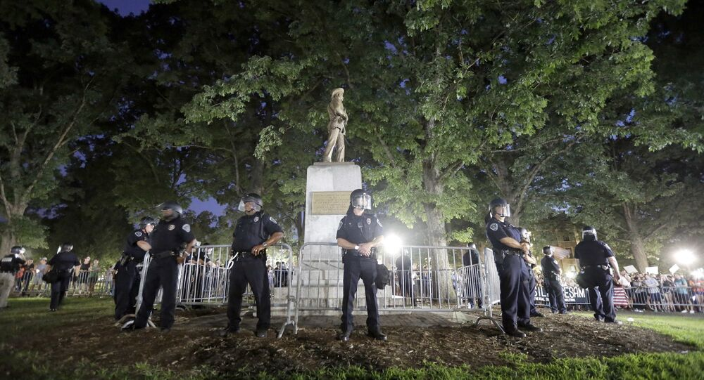 In this Tuesday, Aug. 22, 2017 file photo, police surround the Silent Sam Confederate monument during a protest to remove the statue at the University of North Carolina in Chapel Hill, N.C.