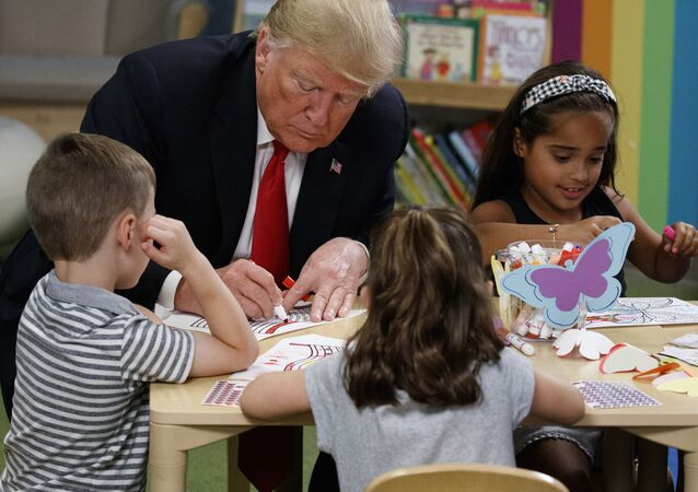 President Donald Trump colors pictures with a group of children at the Nationwide Children's Hospital, Friday, Aug. 24, 2018, in Columbus, Ohio