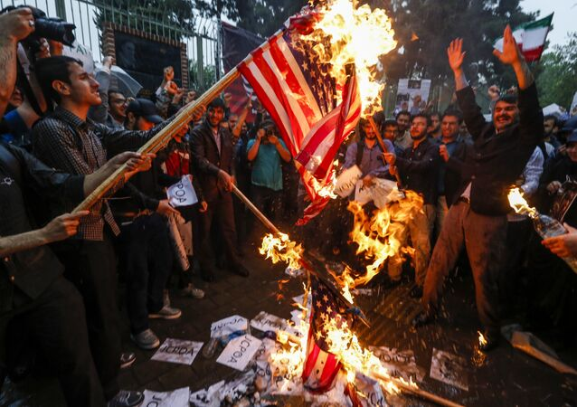 Iranians burn US flags during an anti-US demonstration outside the former US embassy headquarters in the capital Tehran on May 9, 2018.