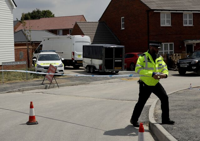 A white van with a trailer is allowed to pass through a police cordon as it drives around the corner before parking outside a property shielded from view that police have been guarding in Amesbury, England, Thursday, July 5, 2018. British officials were seeking clues Thursday in the rush to understand how two Britons were exposed to the military-grade nerve agent Novichok