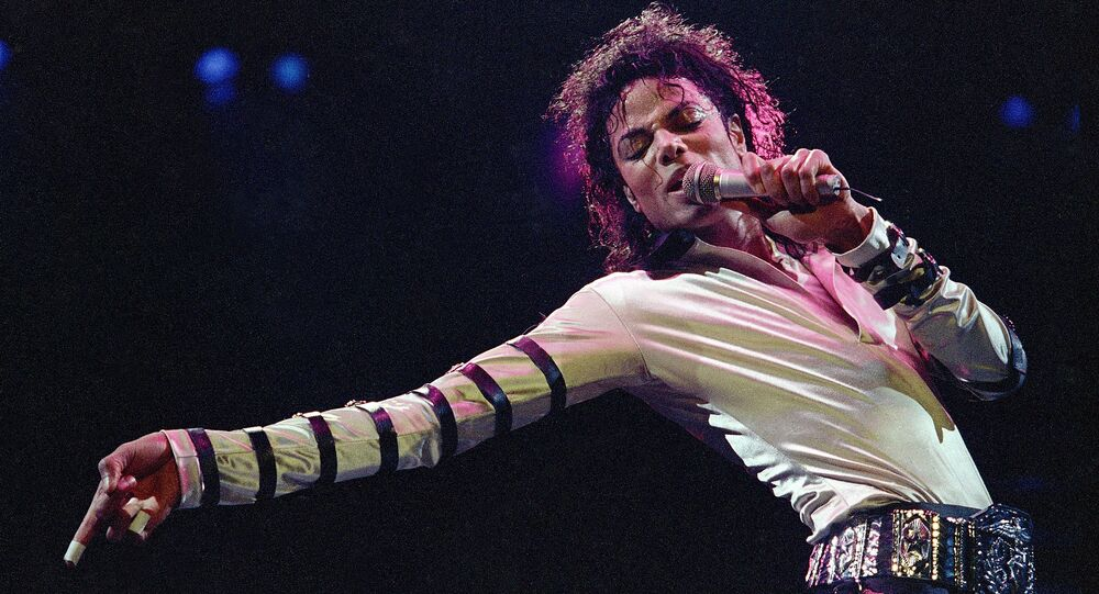 In this Feb. 24, 1988 file photo, Michael Jackson leans, points and sings, dances and struts during the opening performance of his 13-city U.S. tour, in Kansas City
