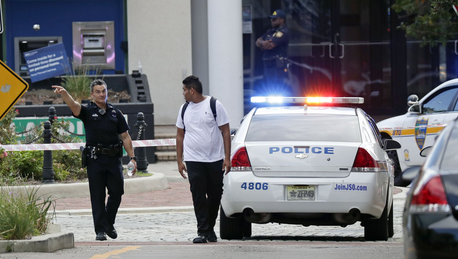 A police officer directs a pedestrian away from a blocked-off area near the scene of a mass shooting at Jacksonville Landing in Jacksonville, Fla., Sunday, Aug. 26, 2018. - Sputnik International, 1920, 08.05.2021