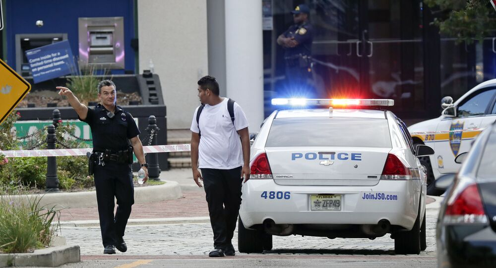 A police officer directs a pedestrian away from a blocked-off area near the scene of a mass shooting at Jacksonville Landing in Jacksonville, Fla., Sunday, Aug. 26, 2018.