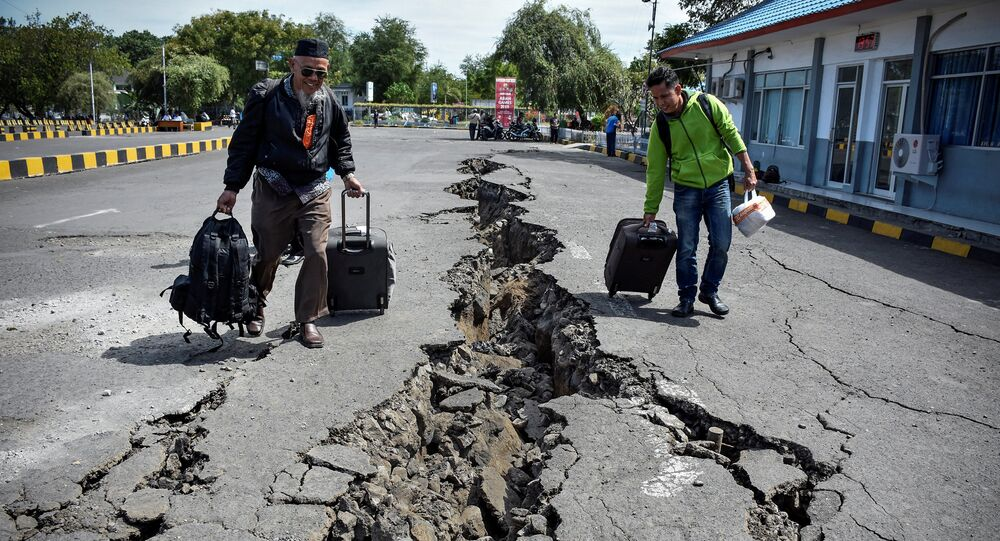 People walk on a road damaged by yesterday's large earthquake at Kayangan Port in Lombok, Indonesia August 20, 2018