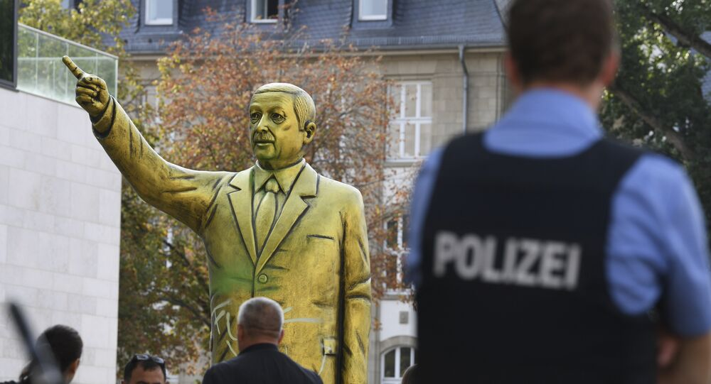 Police and passersby surround a statue showing Turkish President Erdogan which is part of the art festival 'Wiesbaden Biennale' in Wiesbaden, western Germany, Tuesday, Aug. 28, 2018