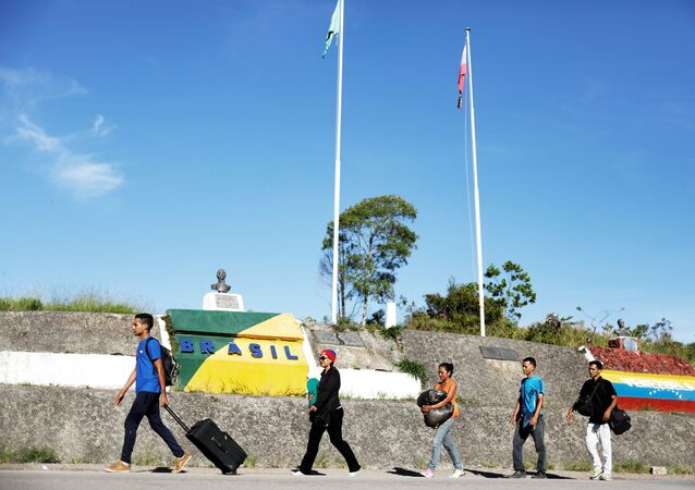 Venezuelans walk across the border from Venezuela into the Brazilian city of Pacaraima