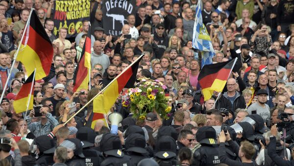 Protesters carry a wreath as they gather for a far-right protest in Chemnitz, Germany, Monday, Aug. 27, 2018 after a man has died and two others were injured in an altercation between several people of various nationalities in the eastern German city of Chemnitz on Sunday - Sputnik International