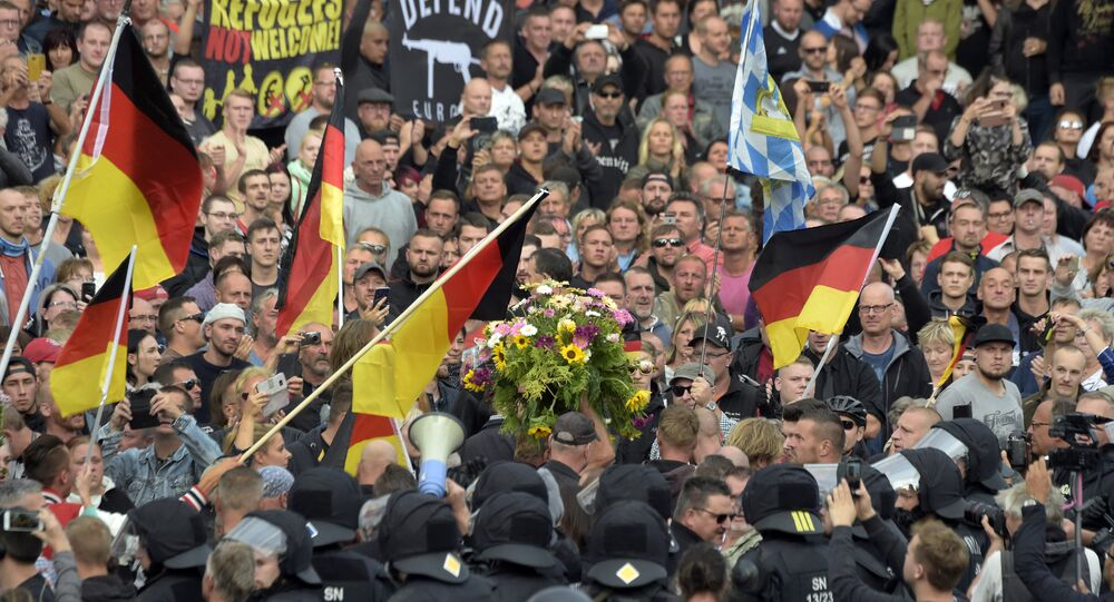 Protesters carry a wreath as they gather for a far-right protest in Chemnitz, Germany, Monday, Aug. 27, 2018 after a man has died and two others were injured in an altercation between several people of various nationalities in the eastern German city of Chemnitz on Sunday